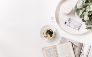 A table with an open book, a coffee and a phone