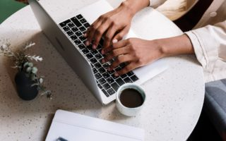 A woman is typing on a laptop on a small circular table looking WordPress plugins