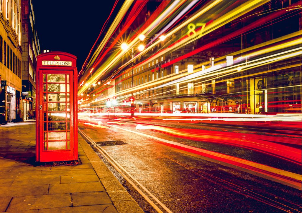 A red phone box next to some speeding vehicles at night