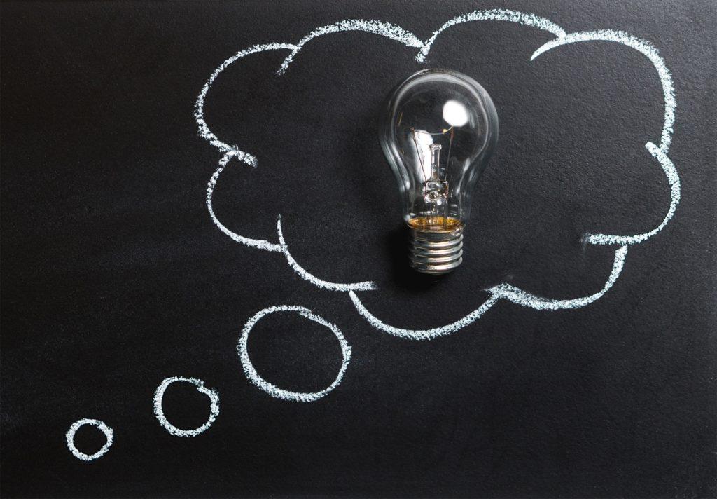 A cloud drawn on a chalkboard with a lightbulb