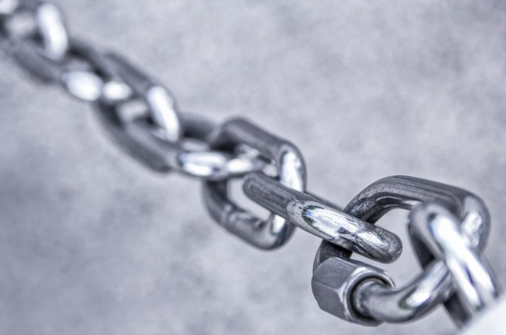 A grey chain of links on a grer