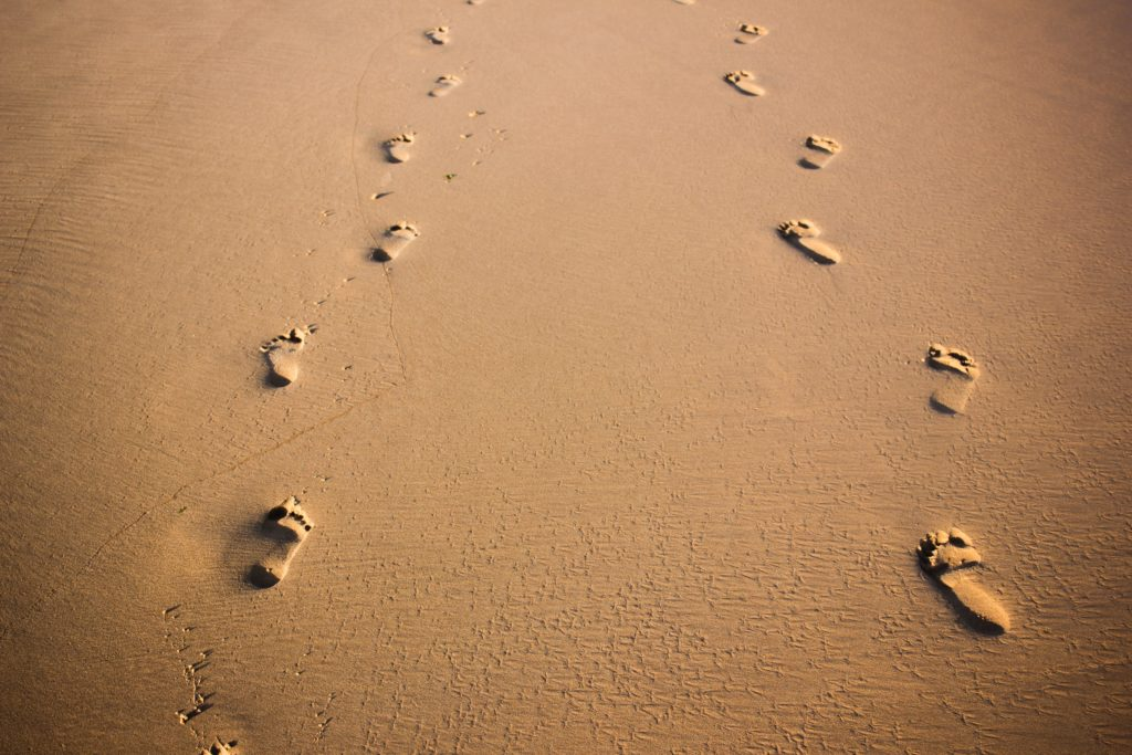 Footprints in the sand that prompts you to follow them