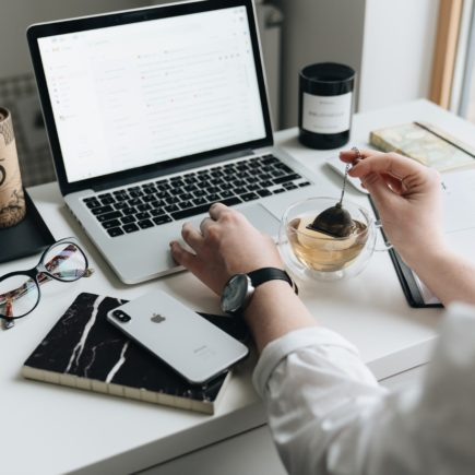 Woman sitting on a desk and looking at a laptop and working on how to get started with email marketing while at the same time is preparing her cup of tea