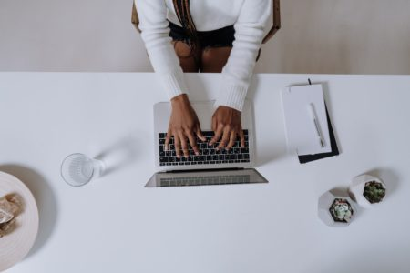 A woman wearing a white sweater is writing her first blog post on a laptop and has a notebook and a glass of water next to her