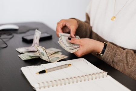 Woman counting money on a desk next to an open notebook with a pen on it that she earned from blogging