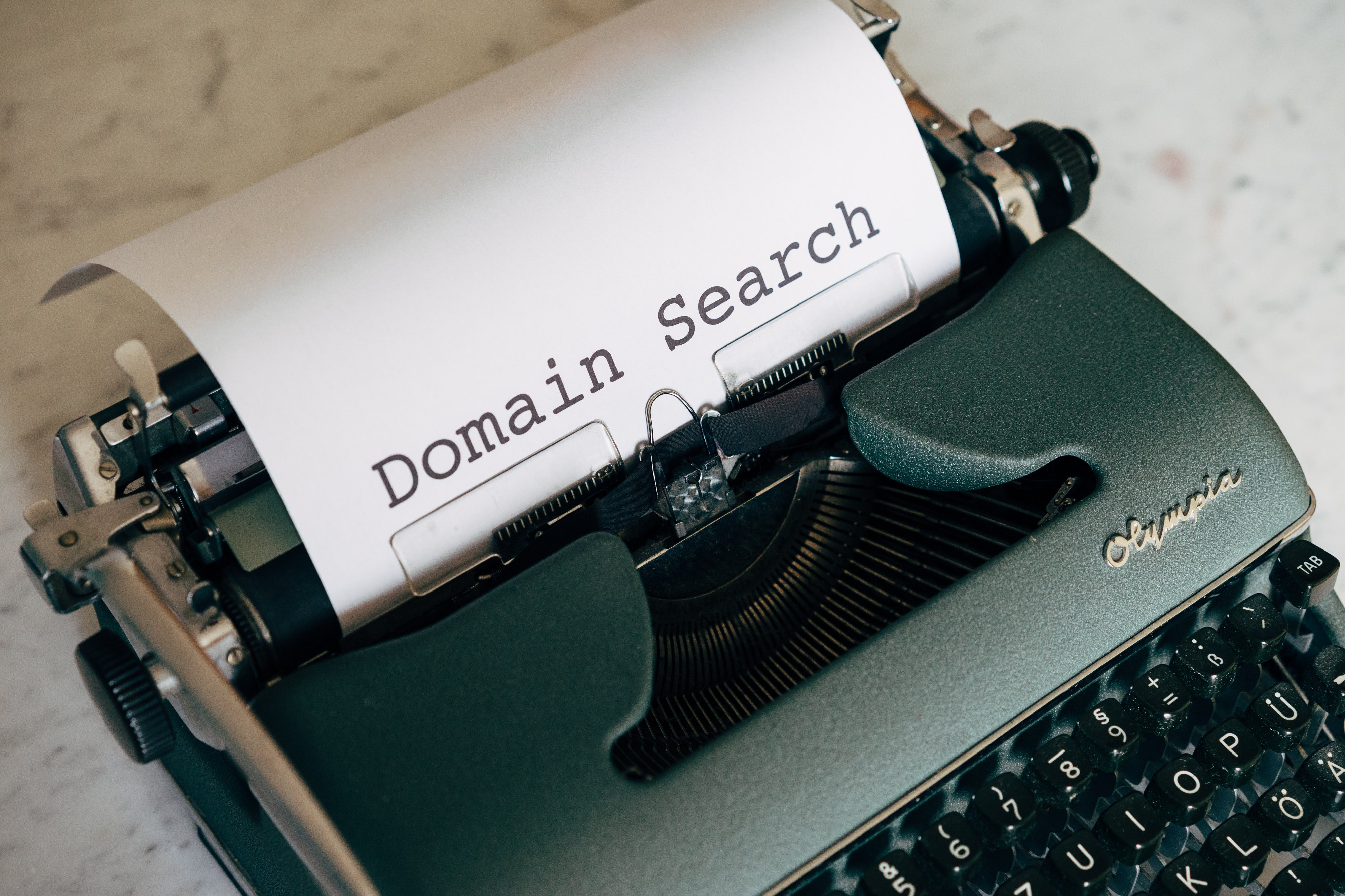 """The words """"Domain Search"""" printed out of an old green type machine"""