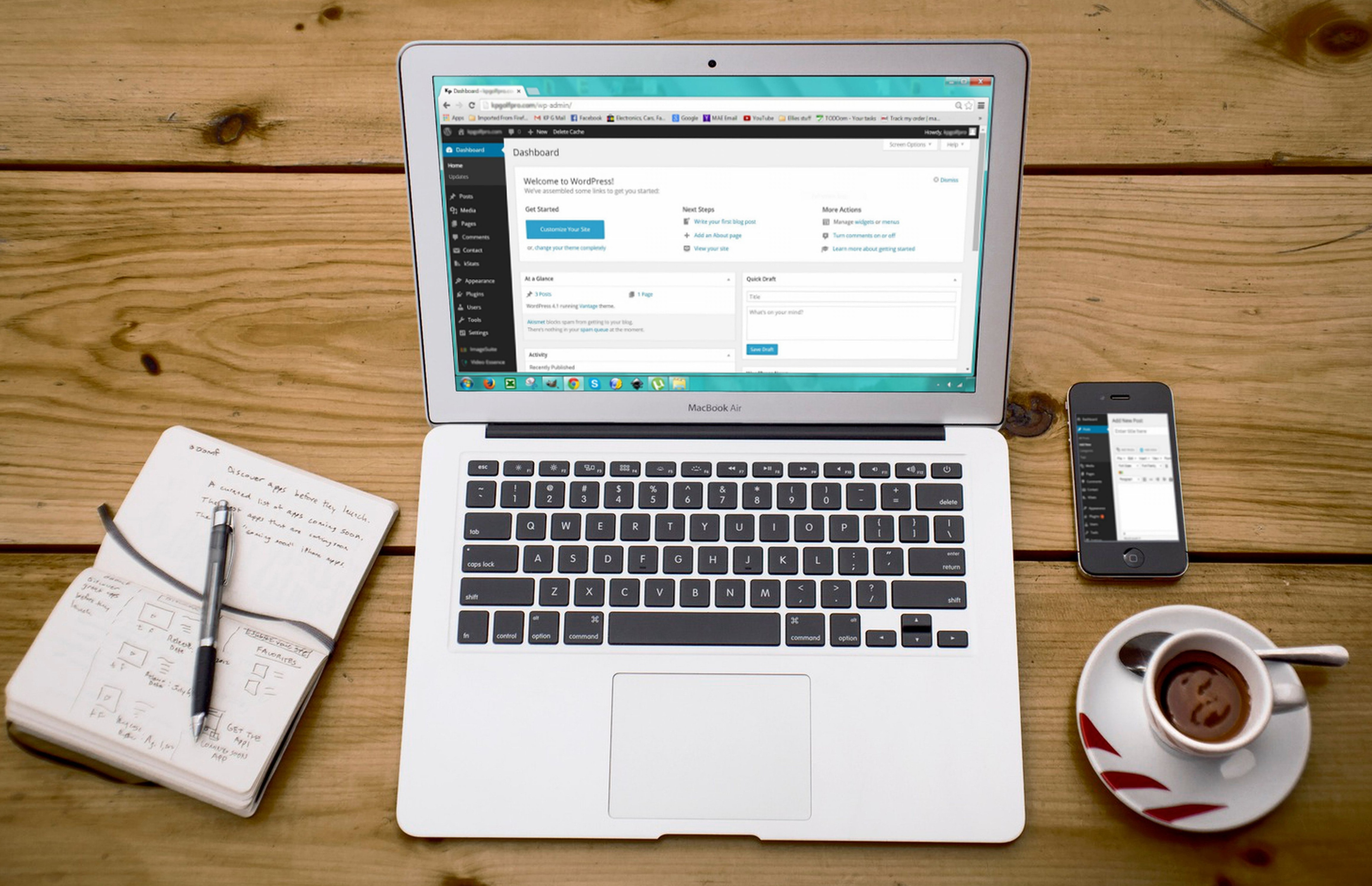 A laptop on a desk showing the WordPress dashboard next to a notebook, a phone and a cup of coffe