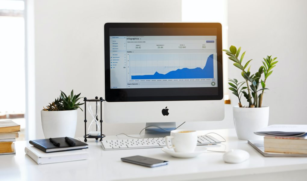 Featured image for guide to set up Google Analytics for WordPress blog showing a computer monitor with a line graph