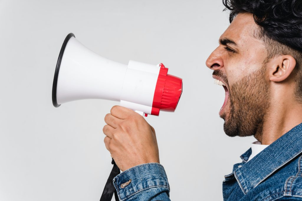 A person is shouting something on red and while megaphone